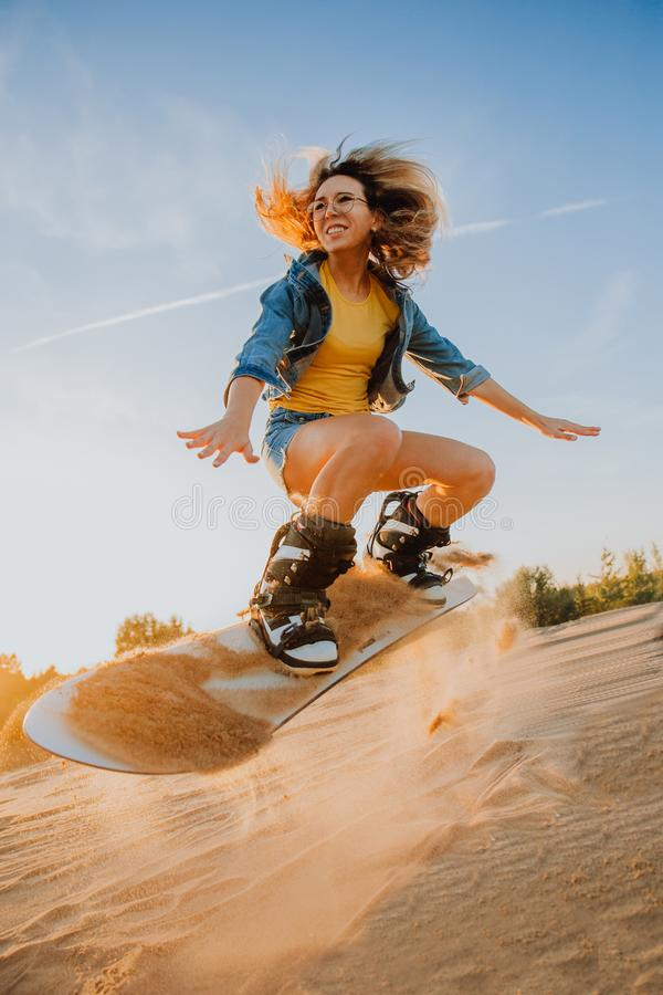 Tourist Sandboarding sexy girl In the Desert Man jumps in and does the trick stock photo