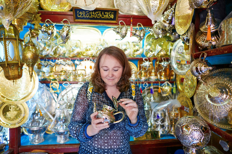 Tourist selecting teapot on Moroccan market stock photography