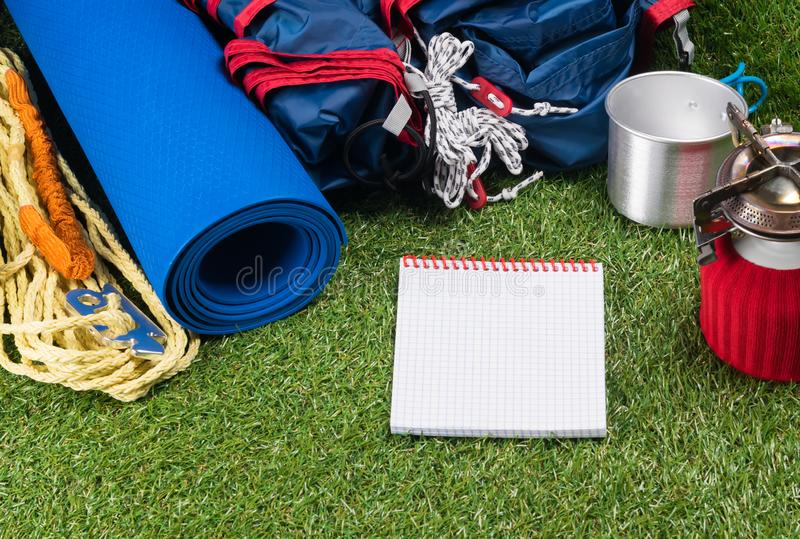 Tourist set on a green lawn for a hike in an expedition, with utensils for cooking food outdoors, with a place for writing, on a w. Hite sheet stock photo