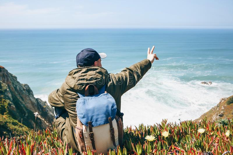 Tourist showing peace sign. Tourist or traveler with a backpack sitting on the shore of the Atlantic Ocean and showing peace sign royalty free stock photos
