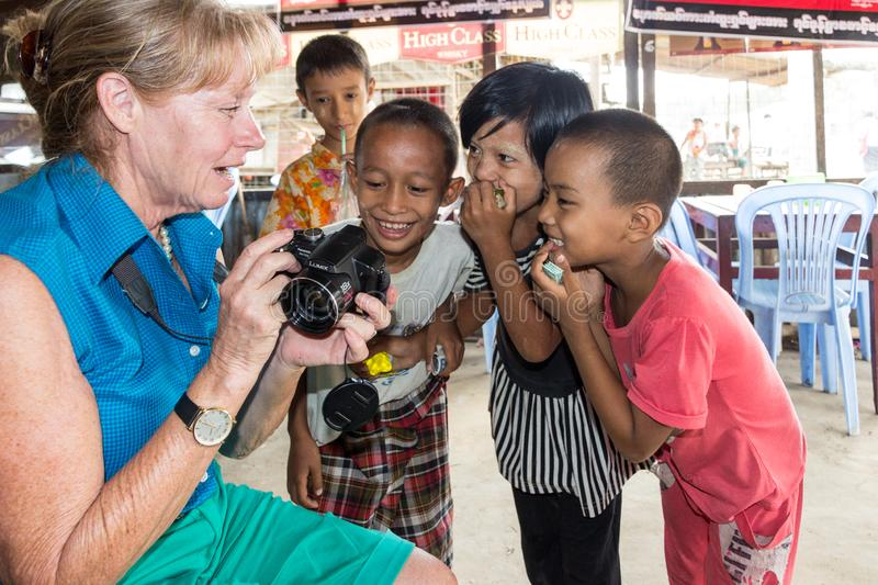 A tourist shows young Burmese children their photo stock images
