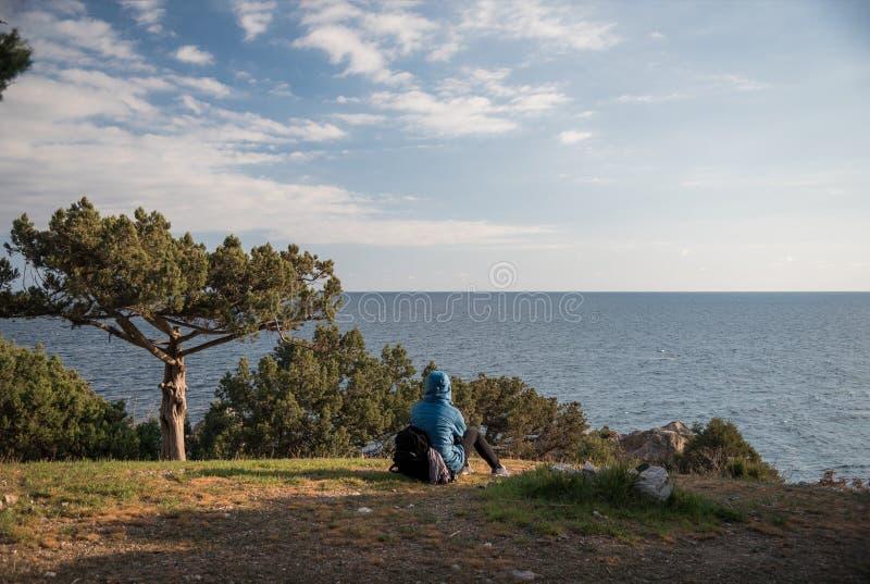 Tourist sitting on the grass near a tree opposite the Black Sea on the southern coast of the Crimea peninsula. Foros, Republic of Crimea - April 1, 2019: Tourist royalty free stock photo