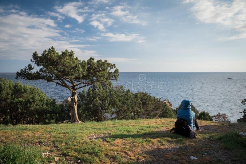 Tourist sitting on the grass near a tree opposite the Black Sea on the southern coast of the Crimea peninsula. Foros, Republic of Crimea - April 1, 2019: Tourist stock photos