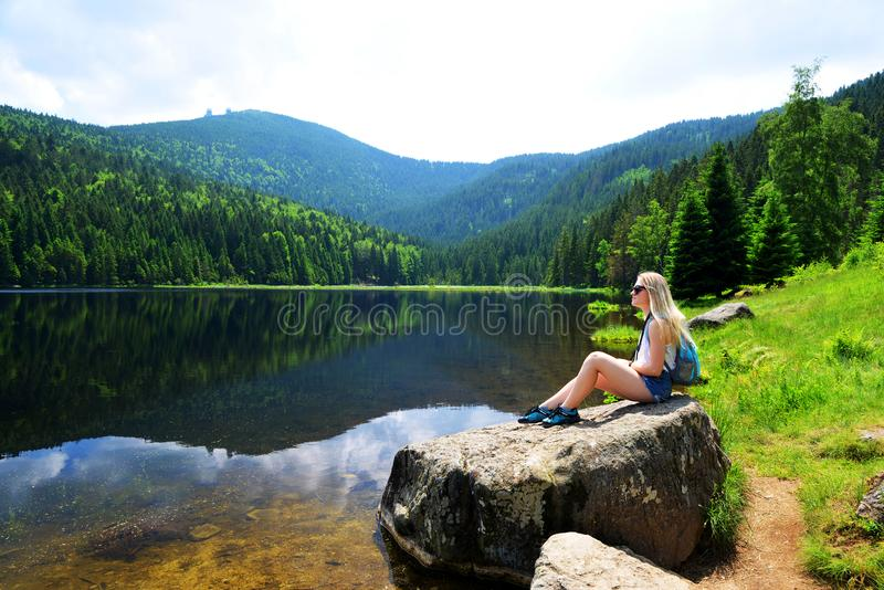 Tourist sitting on stone by moraine lake Kleiner Arbersee, Germany. stock image