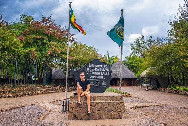 Tourist sitzt auf dem Willkommensschild, das am Eintritt von Victoria Falls, Simbabwe gesetzt wird stockbilder