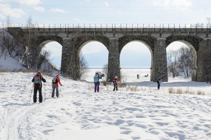 Tourist-Skifahrer gehen unter Eisenbahnbrücke Circum-Baikal lizenzfreie stockfotos