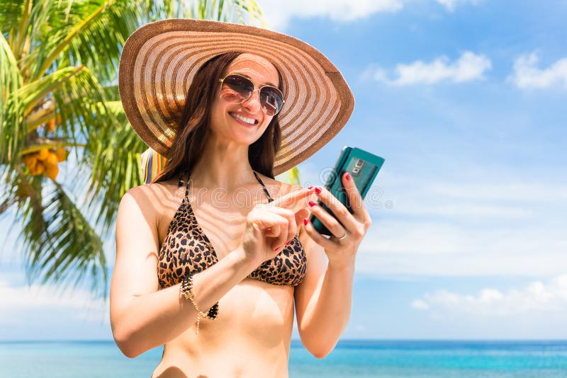 Tourist with smart phone on beach needs data roaming. Tourist woman on vacation with smart phone on palm beach needs data roaming stock photo