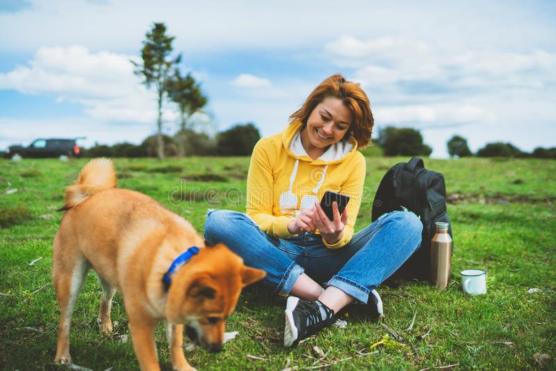 Tourist smile girl on background nature landscape using mobile smartphone with friends dog, person holding in hands gadget techno. Logy, text message on screen royalty free stock photo