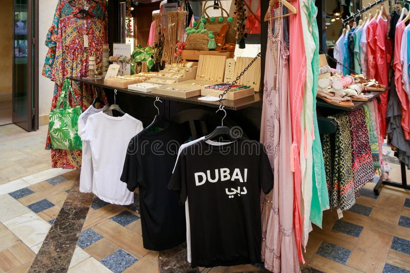 Tourist souvenirs, t-shirts and traditional oriental goods are presented on the counter of a street trading tray. DUBAI, UAE, JANUARY 13, 2019: Tourist souvenirs stock photo
