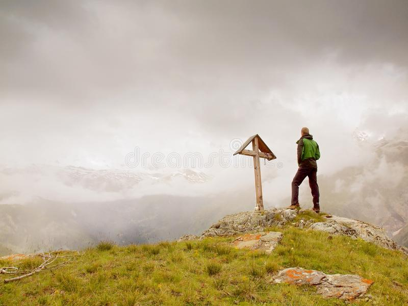 Tourist stand on rocky view point and watching into misty Alpine valley. Wooden cross at a mountain peak stock images