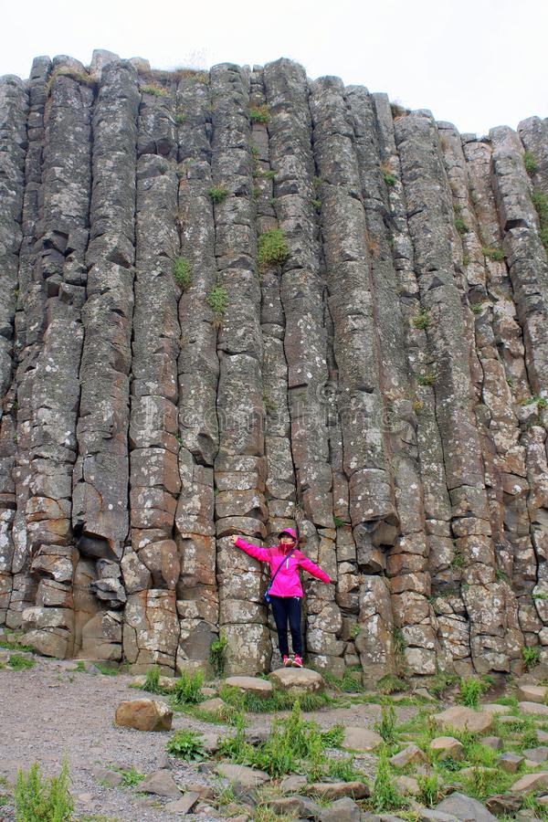 Tourist standing against basalt columns stock images