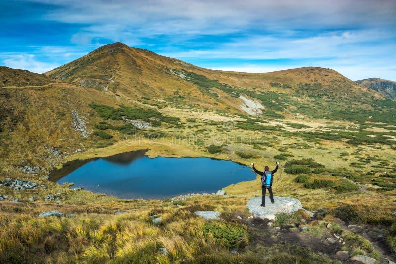 Tourist standing on a big stone near the mountain lake royalty free stock photos