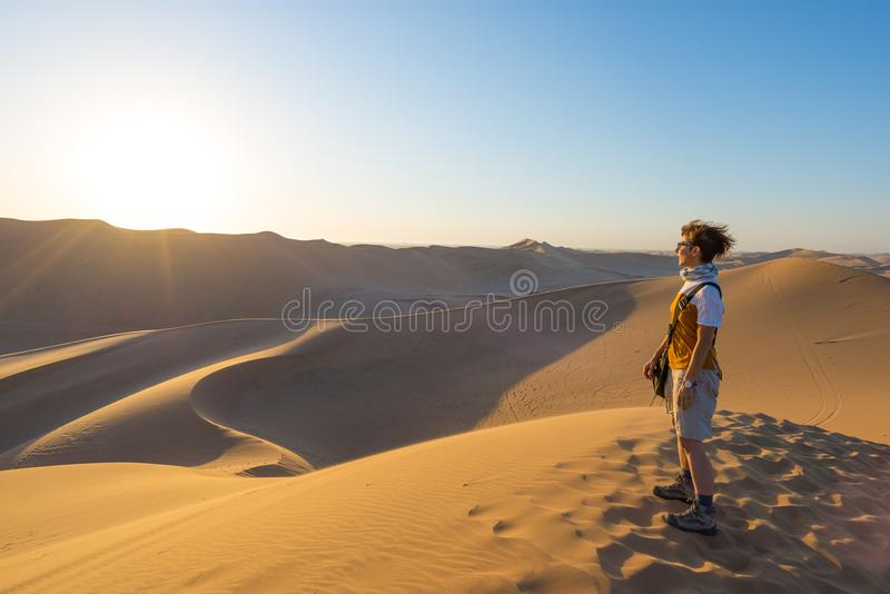 Tourist standing on sand dunes and looking at view in Sossusvlei, Namib desert, travel destination in Namibia, Africa. Concept of stock photography
