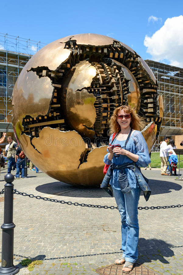 A tourist stands in front of the Sphere within a Sphere in Vatican royalty free stock photo