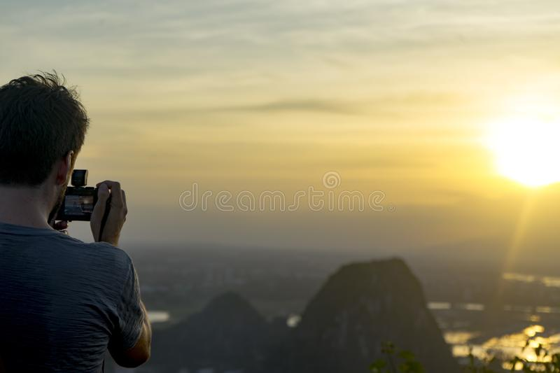 Tourist staying on the top of mountain and taking a photos of Marble mountains stock images