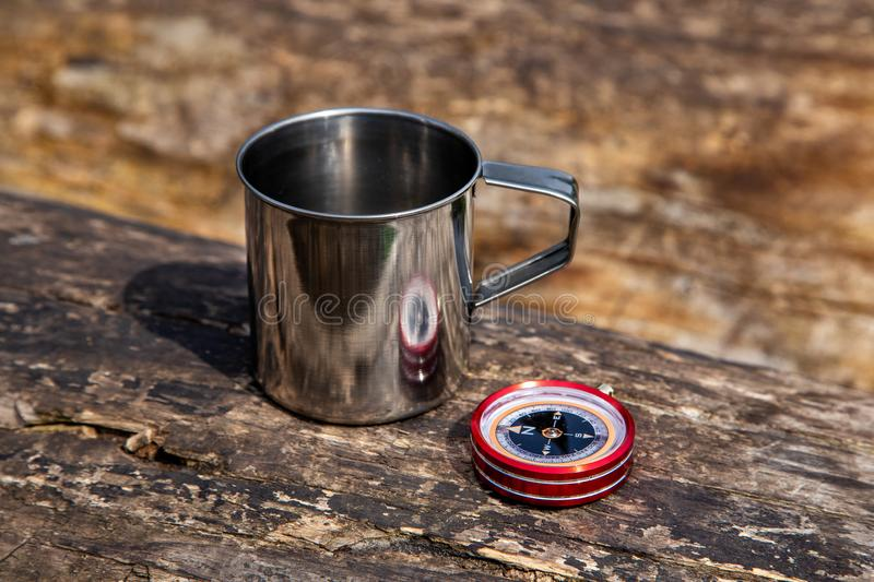 Tourist steel cup and compass in the summer forest.  royalty free stock photos