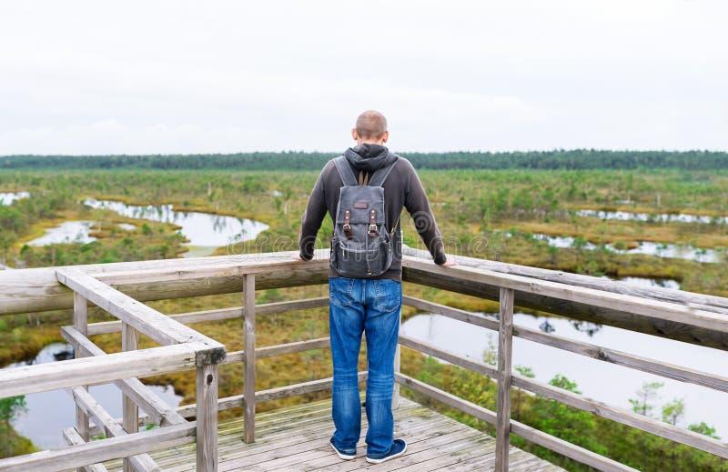 Tourist stoppte auf Brücke mit Rucksack, um Natur am Sommertag zu genießen stockbilder