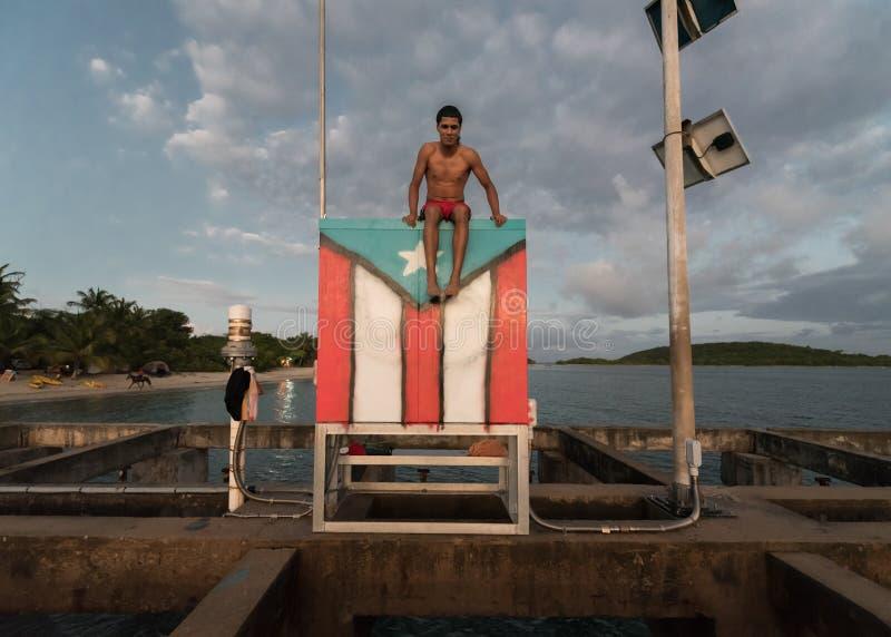 Tourist am Strand, der auf Flagge in Vieques, Puerto Rico sitzt stockfoto