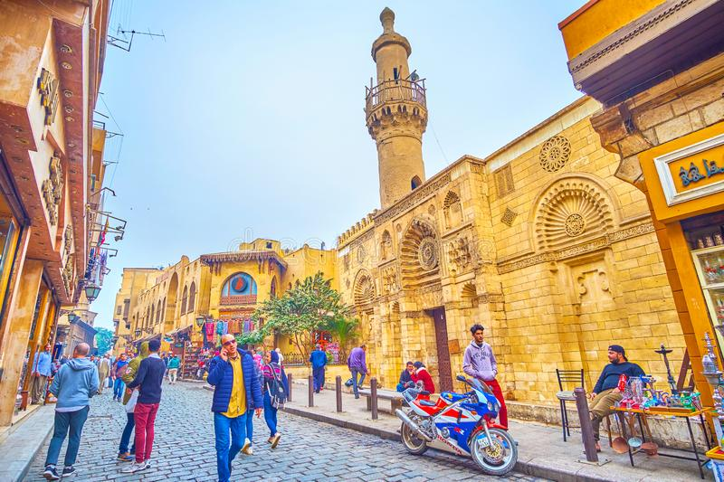 The tourist street with medieval mosque, Cairo, Egypt. CAIRO, EGYPT - DECEMBER 20, 2017: The medieval Al Aqmar Mosque with scenic iwan and adobe minaret in stock photo
