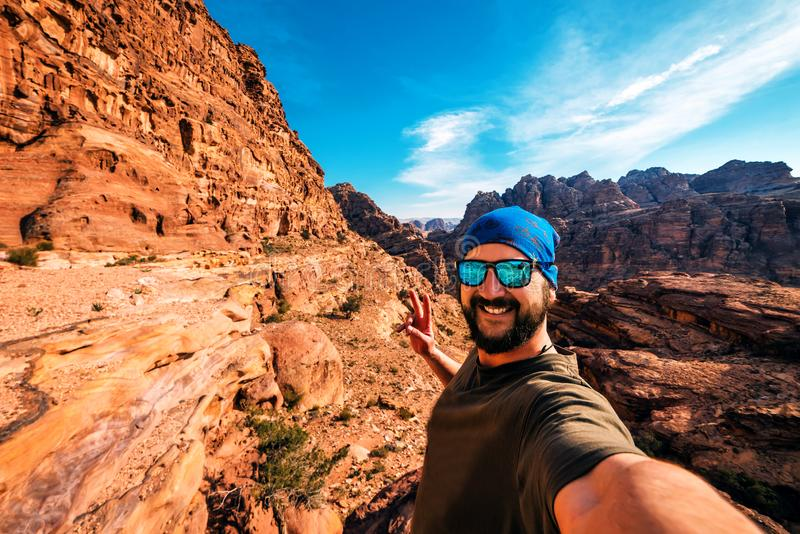 Tourist makes selfie in rocky mountains stock images