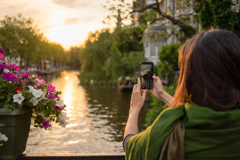 Tourist take photos at sunset. Tourist young woman in Amsterdam take pictures at a beautiful sunset on a bridge stock photo
