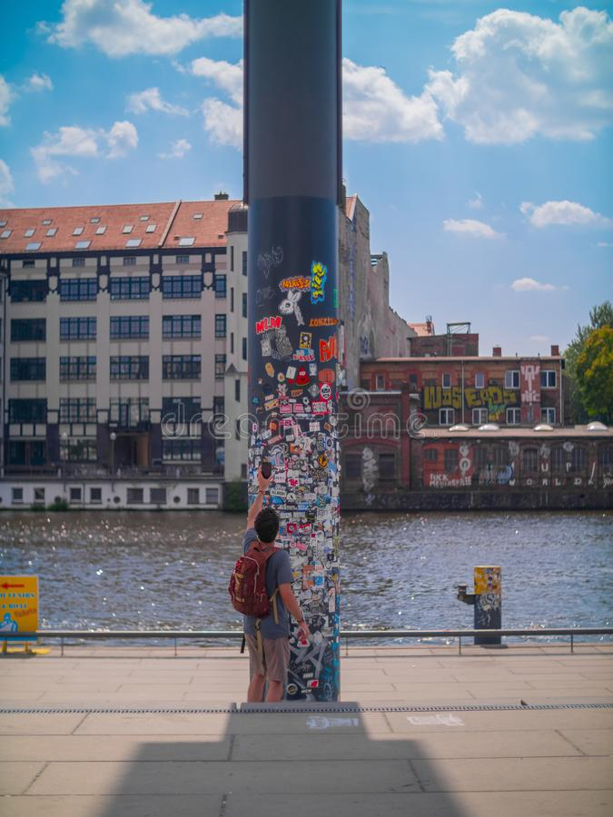 Tourist takes a photo of a sticker covered pole by a river in Berlin stock image