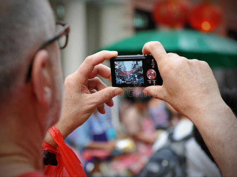 Tourist Takes a Photograph. A tourist takes a photograph of a busy market street in Chinatown on February 4, 2012 in Bangkok, Thailand. Chinese began settling in royalty free stock photos