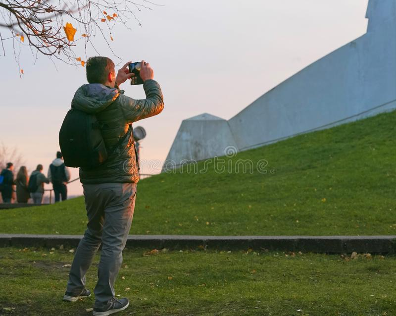 Tourist takes pictures at sunset by phone. stock images