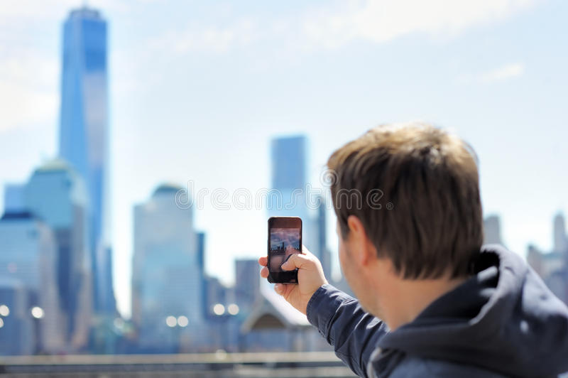 Tourist taking mobile photo of skyscrapers. Middle age tourist taking mobile photo of skyscrapers using his smart phone royalty free stock photography