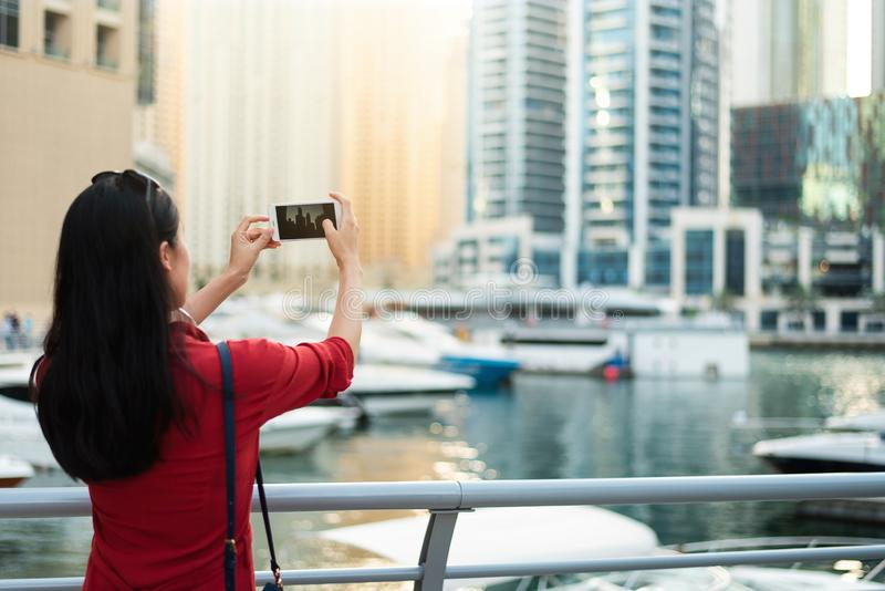 Tourist taking a photo of Dubai marina with smart phone. Tourist taking a photo of Dubai marina with a smart phone woman photographer camera travel girl uae royalty free stock photos