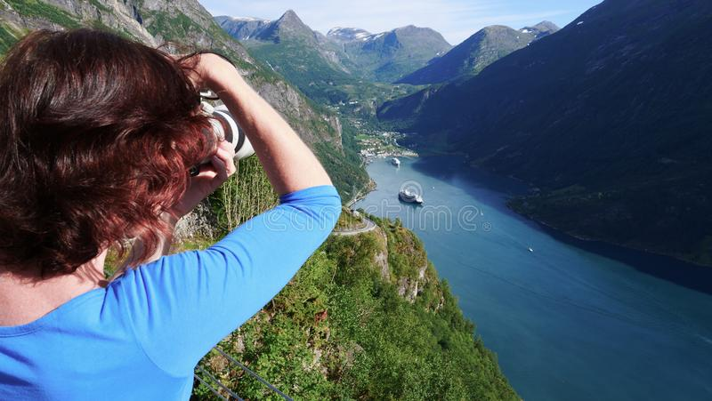 Tourist taking photo of fjord landscape, Norway stock photo