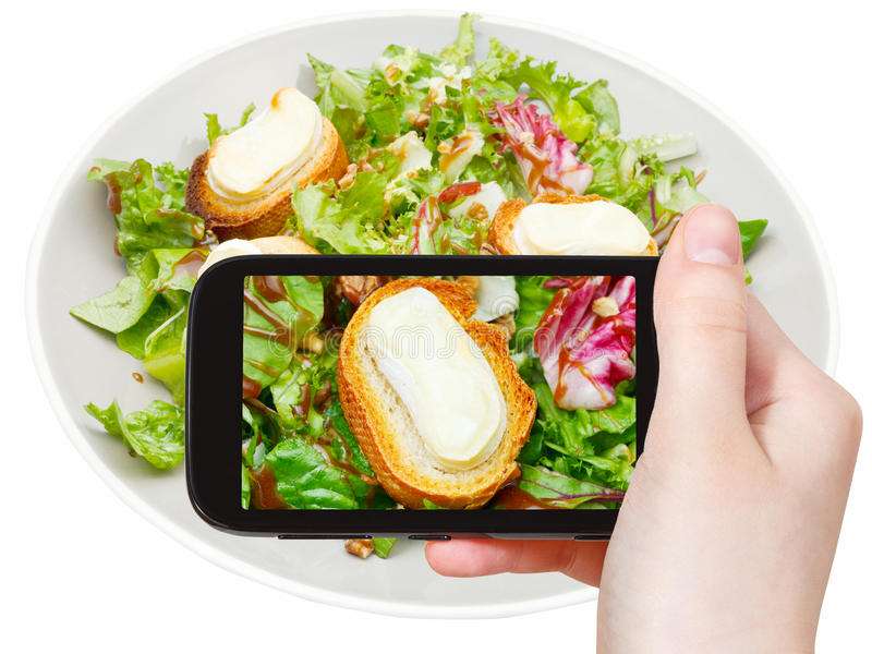 Tourist taking photo of green salad with cheese. Photographing food concept - tourist taking photo of green salad with goat cheese on mobile gadget, Italy stock photos