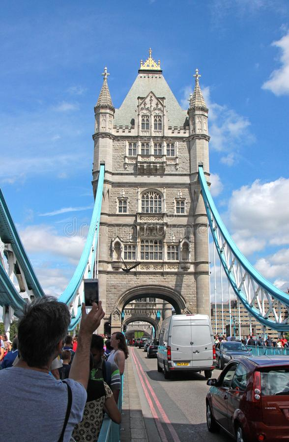 Tourist taking a photo with mobile/call phone while a very busy Tower Bridge royalty free stock photo