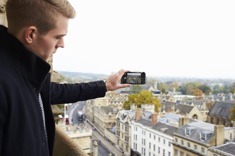 Tourist Taking Photo Of Oxford Skyline On Mobile Phone royalty free stock photos