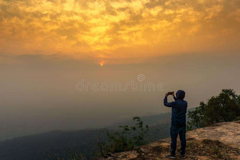 Tourist taking picture of sunrise sky nature background. Lone traveler man stand on the cliff taking pictre of panorama golden hour sky scene with mobile phone royalty free stock image