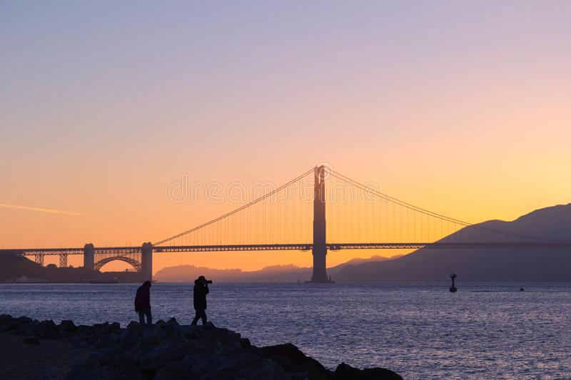 Tourist taking picture of  sunset over Golden Gate Bridge, San Francisco, California stock image