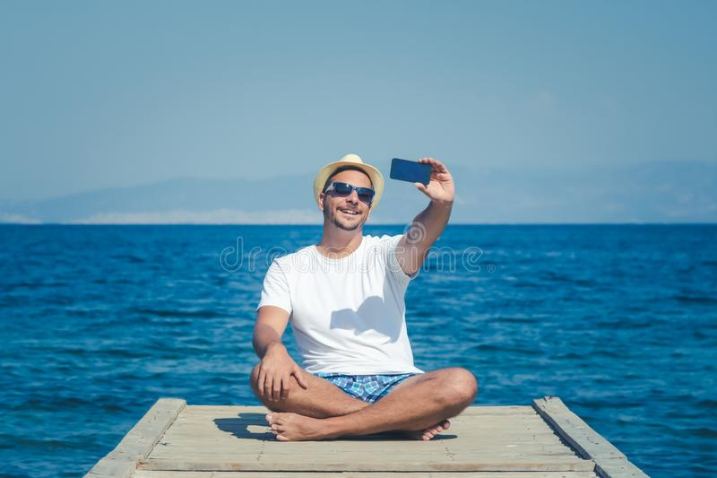 Young man in hat and sunglasses sitting on pier and taking selfie with smartphone. Sea in the background. Summer vacation concept. Tourist taking self portrait stock image