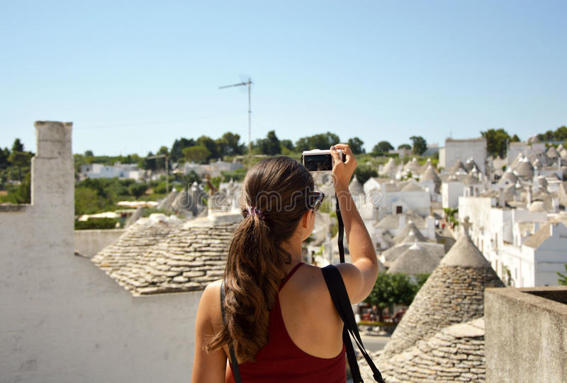 Tourist taking travel picture with mirrorless camera of Alberobello trulli cityscape during summer holidays. Unrecognizable female stock images