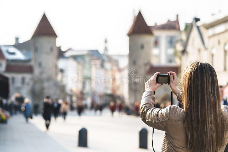 Tourist in Tallinn taking photo of Viru Gate. royalty free stock photography