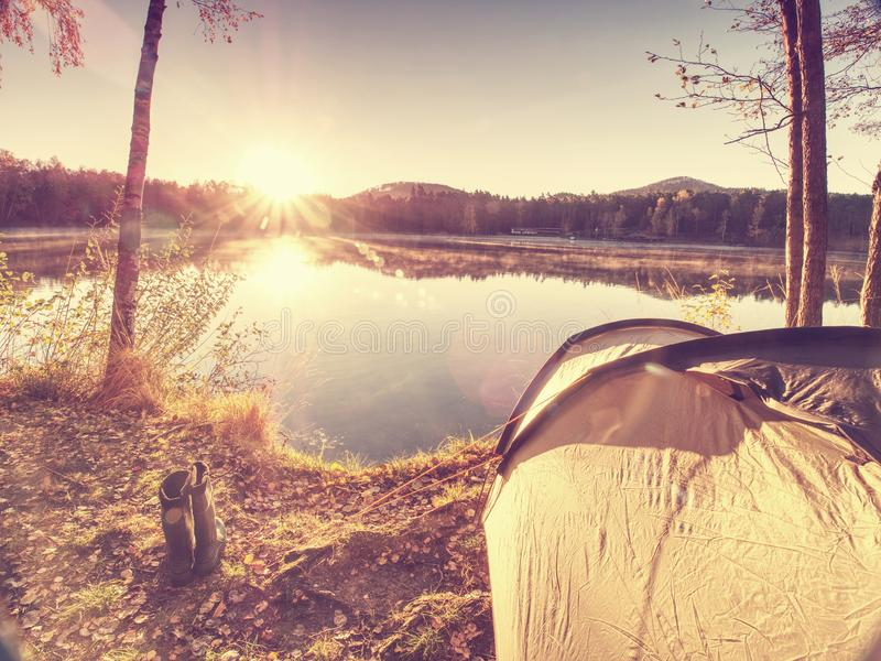 Tourist tent. Camping bellow trees at the river. Bank. Summer sunny morning at lake watercourse valley twilight trip trekking travel tourism toughness stone royalty free stock image