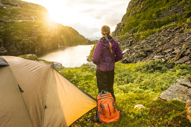 Tourist tent and woman in mountains sunset Norway royalty free stock image