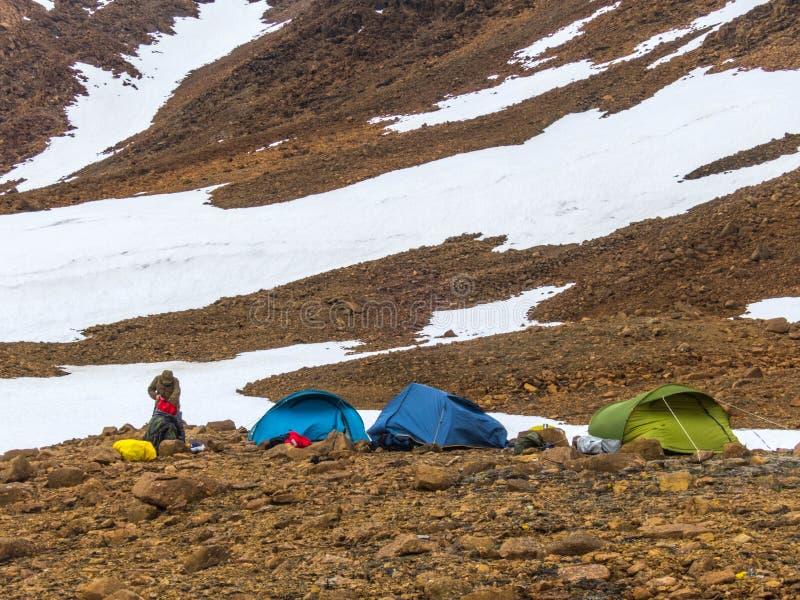 Tourist tents in the mountains. Beautiful mountain landscape. Panorama. Snowy peak. Polar urals mountains. Yamal stock image