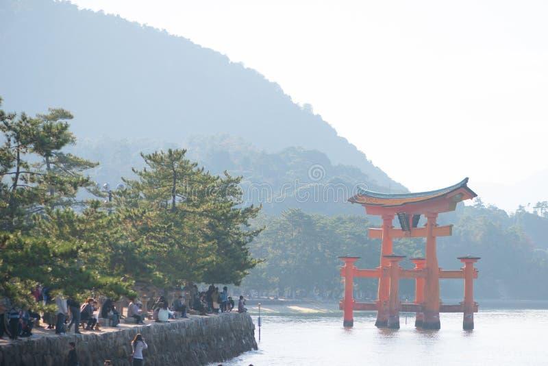 Tourist to see Floating torii gate of Itsukushima Shrine in autumn season at Miyajima island. Hiroshima, Japan royalty free stock image