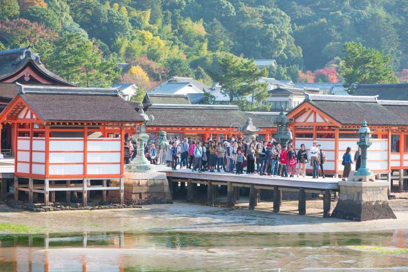 Tourist to see Floating torii gate of Itsukushima Shrine in autumn season at Miyajima island. Hiroshima, Japan stock photography