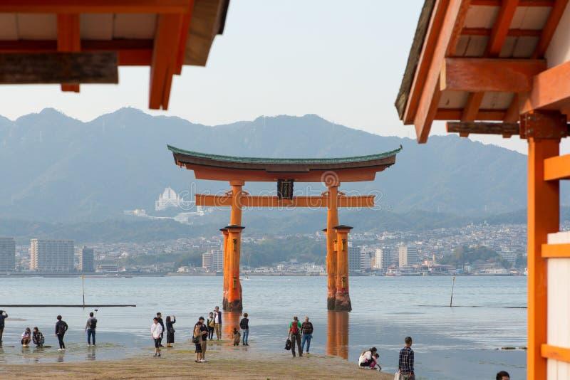 Tourist to see Floating torii gate and pray of Itsukushima Shrine at Miyajima island. Hiroshima, Japan royalty free stock image