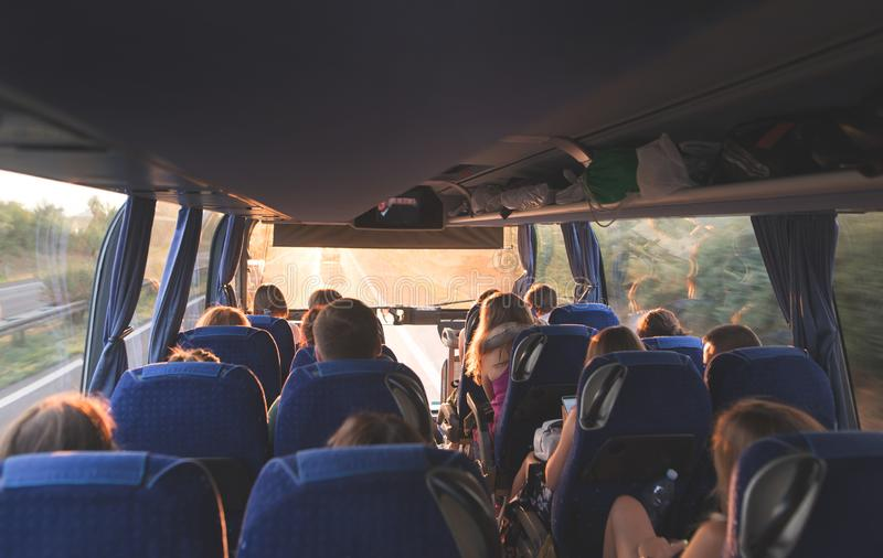 tour on the bus. People travel by bus. Salon of the great tourist bus with people at sunset royalty free stock images