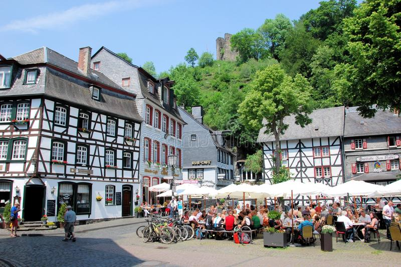 Monschau, Tourist town with half-timbered houses -. Market place historic city Monschau with terraces and people, half-timbered houses and ruins, Germany, North royalty free stock image
