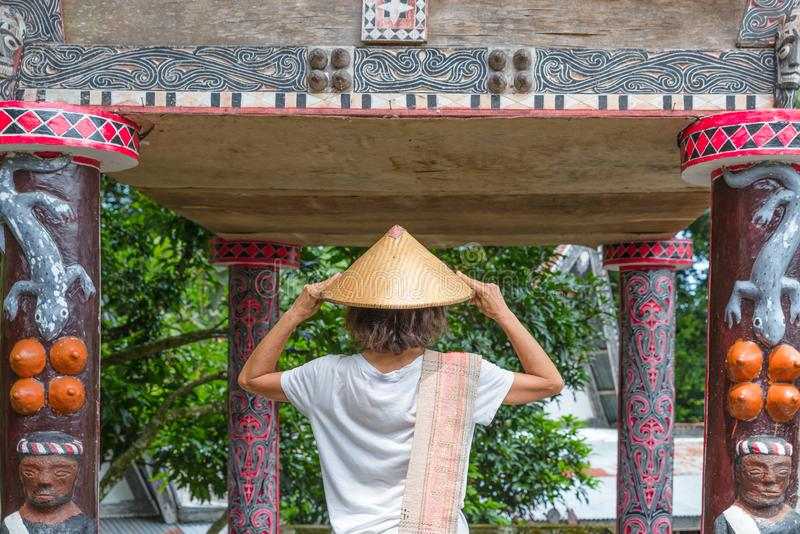 Tourist with traditional asian hat visiting Batak traditional village and Old Tomb of King Sidabutar in Tomok lake Toba, famous royalty free stock photo