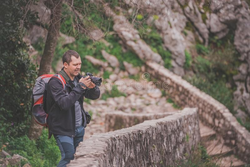 Tourist on a trail checking images on camera. Male tourist on a trail above Kotor Bay checking images at the back screen of his camera stock image