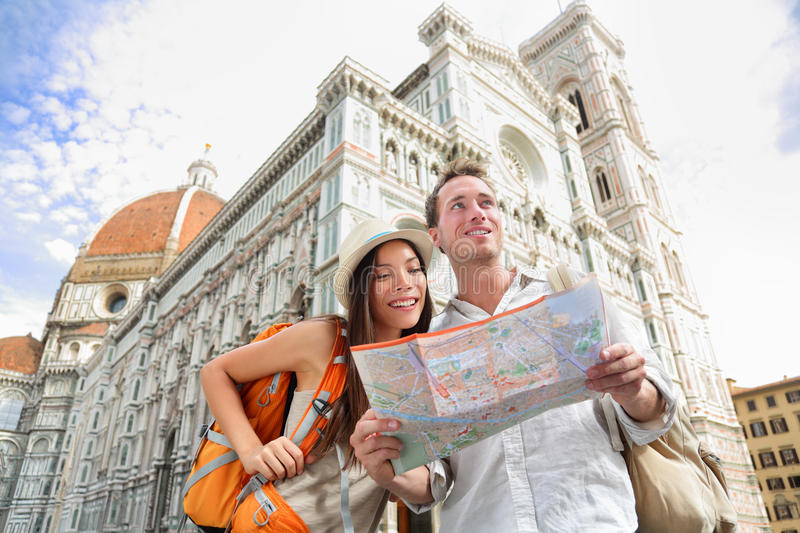 Tourist travel couple by Florence cathedral, Italy. Looking at map in front of Il Duomo di Firenze also called Basilica di Santa Maria del Fiore. Main tourist